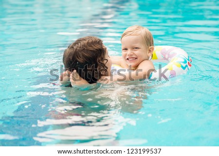 Mom helping her child swimming in deep waters without fear