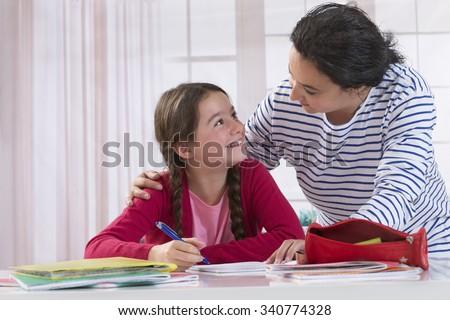 Mom helping her daughter do homework