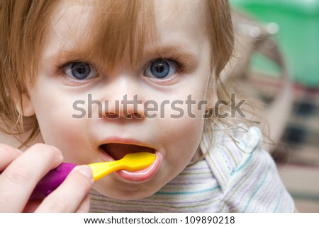mom helping out a little girl with a toothbrush