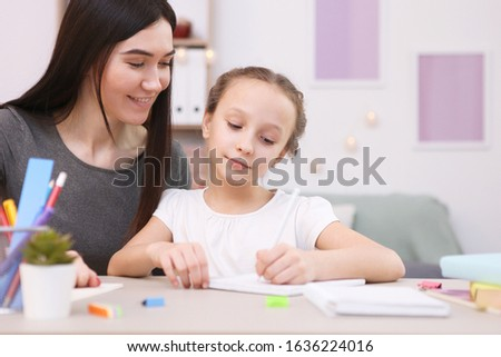 Mom helps the girl to do homework. Children and parents.