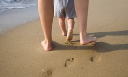 mom helps to make the child's first steps on the beach