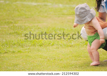 Mom holding little baby trying to walk