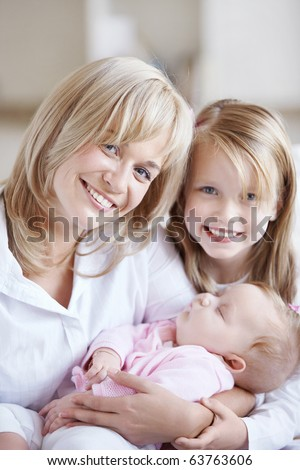 Mom holding the baby in her arms and her daughter