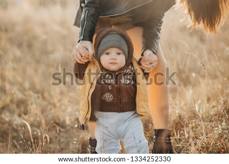 mom holds her baby boy by the hands for a walk in the fall in nature. Baby's first steps