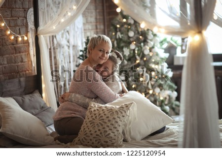 Mom hugs and kisses teen daughter. The concept of warm relations on the eve of Christmas and New Year. #1225120954
