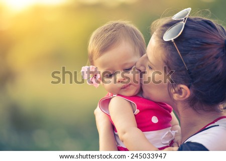 mom is kissing child on...