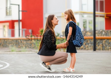 Mom leads her daughter to school. Return to school. Woman and girl with backpack behind the back. Beginning of lessons. First day of fall. ストックフォト ©