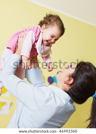 mom lifting her daughter up and smiling. Vertical shape