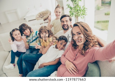 Mom makes selfie picture photo with big family for her blog, sit on white comfort, cozy sofa or couch in modern light interior apartment #1197877663