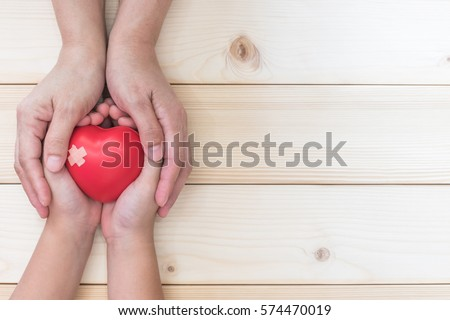 Mom, mother holding daughter or son child kid's hand supporting red heart love with cross bandage on wood for nursing children home day care health care and hospital medical business concept