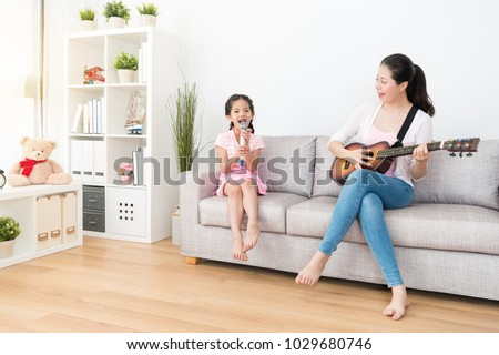 Mom plays the wooden guitar daughter sing the songs. They have a warm family time over the weekend. #1029680746