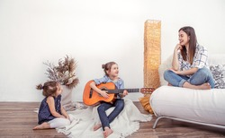 Mom plays with her daughters at home. Lessons on a musical instrument, guitar. Children's development and family values. The concept of children's friendship and family .