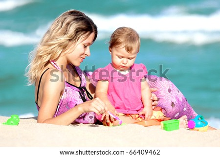 Mom plays with the child on the beach - stock photo