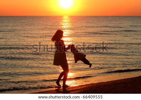 Mom plays with the child on the beach