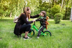 Mom praises and pats his young son for success in cycling, mother always tries to cheer her son that he was a good self-esteem. It is clear that the boy is very happy and easily accepts praise