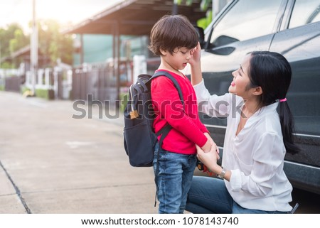 Mom preparing to send her children back to school at car in morning. Education and Back to school concept. Happy family and Loving of people theme.