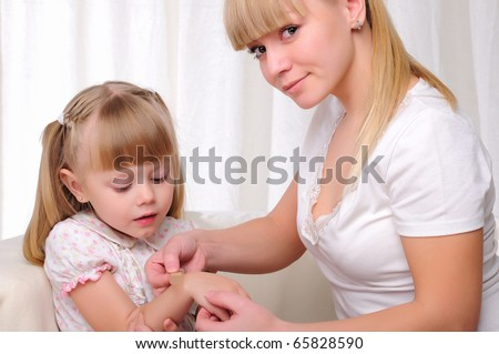 Mom puts her baby daughter plaster on the sore arm
