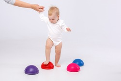 mom's hand holding baby girl in white bodysuit with physiotherapy tools for flat feet-balance pod on white background