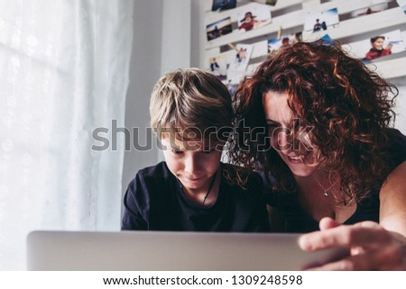 Mom son watch video computer smiling. Curly woman with blond child have fun playing with student pc. Looking homework information helped by mother at home. Family domestic scene White modern furniture