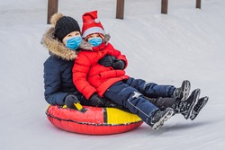 mom son wearing a medical mask during COVID-19 coronavirus ride on an inflatable winter sled tubing. Winter fun for the whole family
