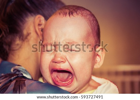 Mom soothes baby. The baby is crying