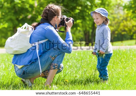 Mom takes pictures of a child in the park in summer #648655441