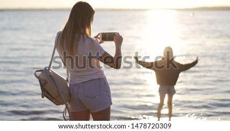Mom takes pictures of her daughter on the background of the sunset. Cute girl dancing by the lake. Sun kissed child.