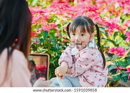 Mom takes pictures of her daughter on vacation traveling time. Cute little asian girl smiling happy face when taking photo
