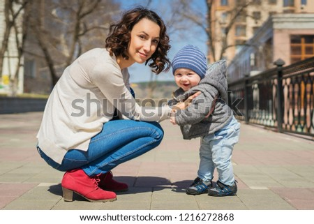 Mom teaches baby to walk on the street. Mom supports her son with her hands, teaches him to stand. A little boy learns to walk. #1216272868