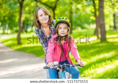 mom teaches her daughter to ride a bicycle in the park #1157373151