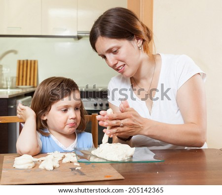 Mom teaches the girl to mold dough figurines in the room