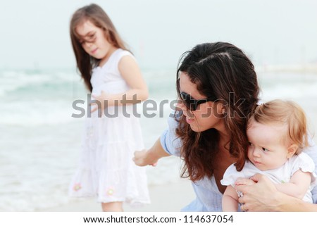Mom tries to hold two her daughters in the open arms. eldest daughter offended.
