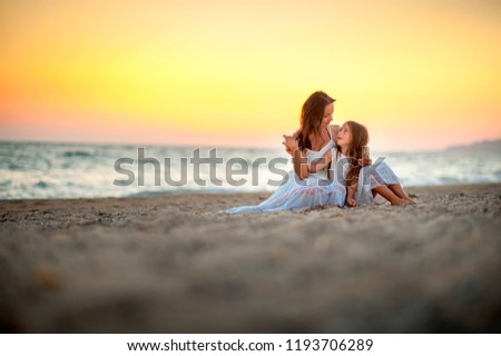 Mom with a little daughter on the beach at sunset, sitting on the sand and resting
