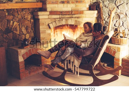 Stock Photo Mom with child reading book and relaxing by the fire place some cold evening, winter weekends, cozy scene