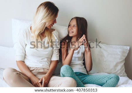 Mom with her tween daughter relaxing in bed, positive feelings, good relations. #407850313