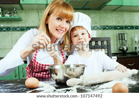 Mom with son cooking and baking in kitchen