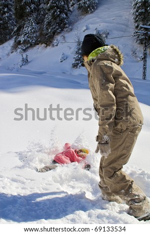 Mom with the child tyuey igrayut in the snow