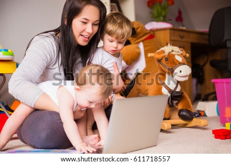 Mom works at a laptop with children #611718557