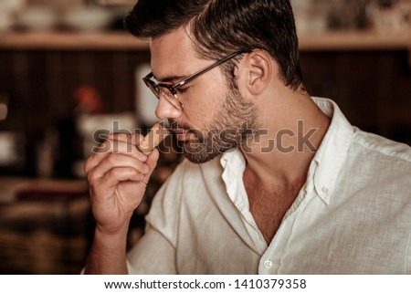 Moment enjoyment. Handsome male person keeping eyes closed while enjoying the taste of wine