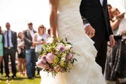 Moment in wedding,  bride and bridegroom holding hands with bouquet and wedding guests in background
