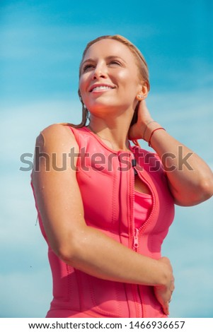 Moment of joy. Closeup portrait of a joyful Caucasian blonde woman with wet blonde hair in a wet life vest standing outdoors with the blue cloudless sky in background