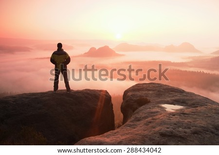 Moment of loneliness. Man on the rock empires  and watch over the misty and foggy morning valley.