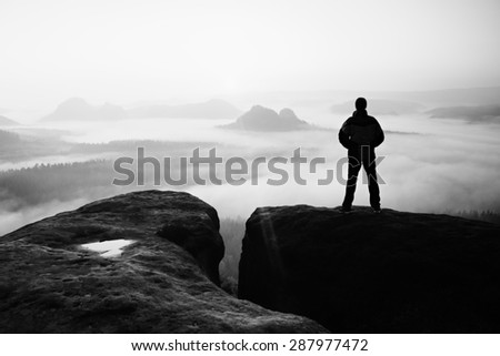 Moment of loneliness. Man on the rock empires  and watch over the misty and foggy valley.