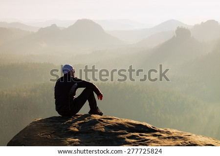 Moment of loneliness. Man sit on the peak of rock and watching into colorful mist and fog in forest valley.