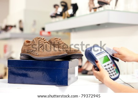 Moment of payment using credit card terminal in shoe store. Selective focus on pair of male shoes on top of box.