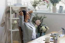 Moment of relax. Serene businesswoman florist owner of flower delivery service rest of computer work. Smiling calm lady floral decor specialist hold hands behind head enjoy quietness breath fresh air