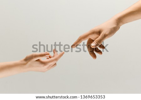 Moment of weightless. Two male hands trying to touch like a creation of Adam sign isolated on grey studio background. Concept of human relation, community, togetherness, symbolism, culture and history #1369653353
