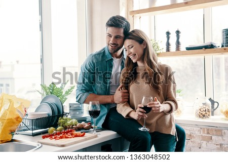 Moments of intimacy. Beautiful young couple cooking dinner and drinking wine while standing in the kitchen at home