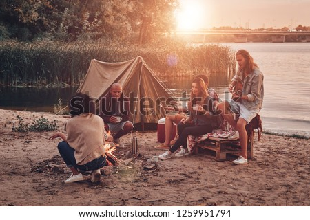 Moments of joy. Group of young people in casual wear smiling while enjoying beach party near the campfire #1259951794