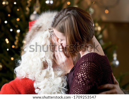 Mommy kissing Santa Claus by the Christmas tree